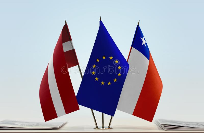 Flags of Latvia EU and Chile. Desktop flags of Latvia and Chile with European Union flag in the middle royalty free stock images