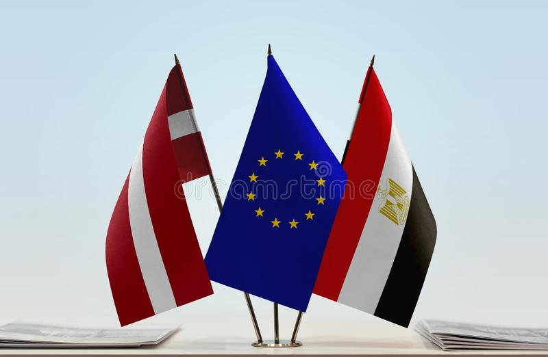 Flags of Latvia EU and Egypt. Desktop flags of Latvia and Egypt with European Union flag in the middle royalty free stock photography