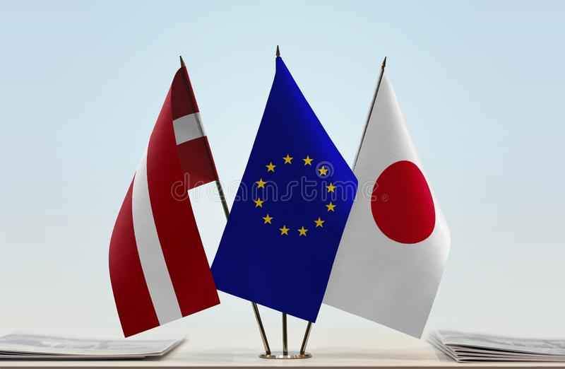 Flags of Latvia EU and Japan. Desktop flags of Latvia and Japan with European Union flag in the middle royalty free stock photos