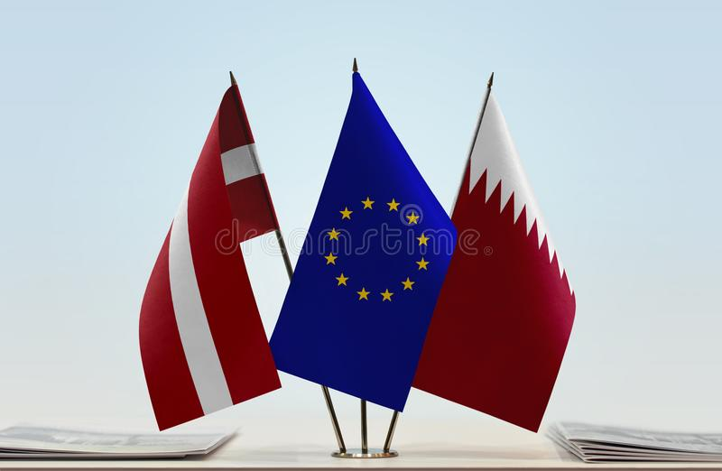 Flags of Latvia EU and Qatar. Desktop flags of Latvia and Qatar with European Union flag in the middle royalty free stock image