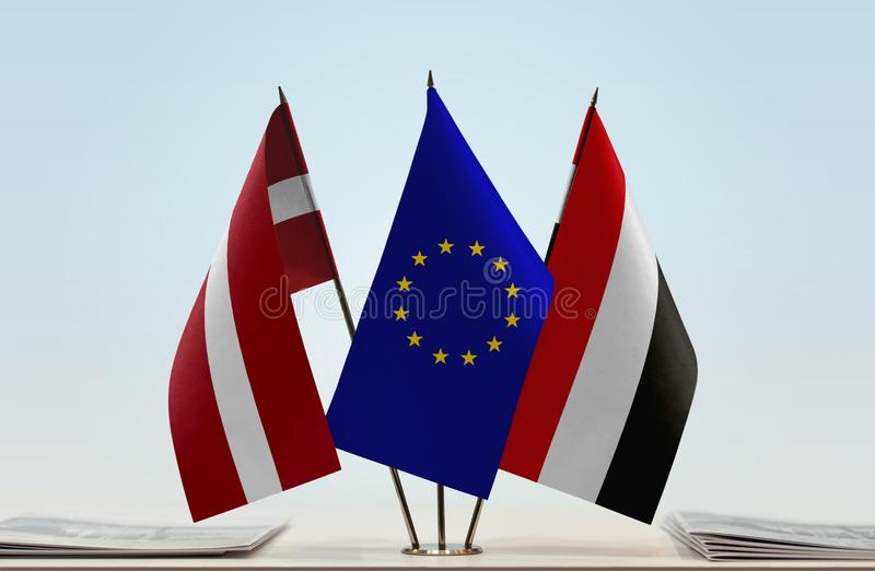 Flags of Latvia EU and Yemen. Desktop flags of Latvia and Yemen with European Union flag in the middle royalty free stock photography