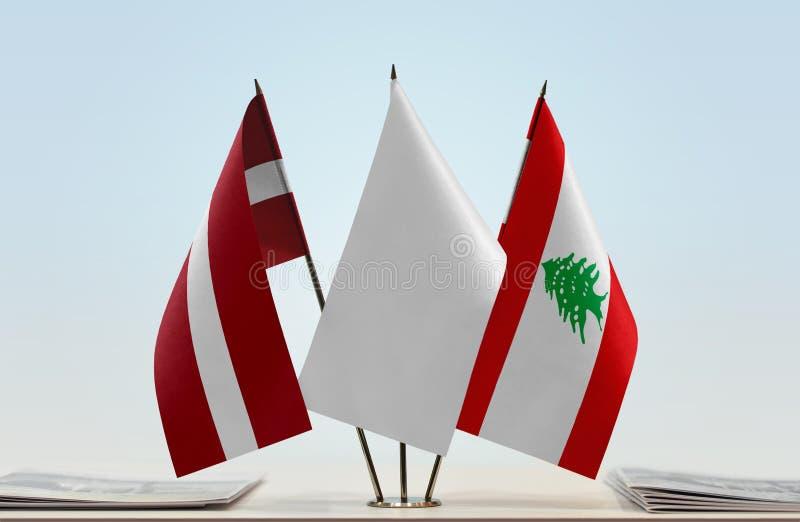 Flags of Latvia and Lebanon. Desktop flags of Latvia and Lebanon with white flag in the middle stock photo