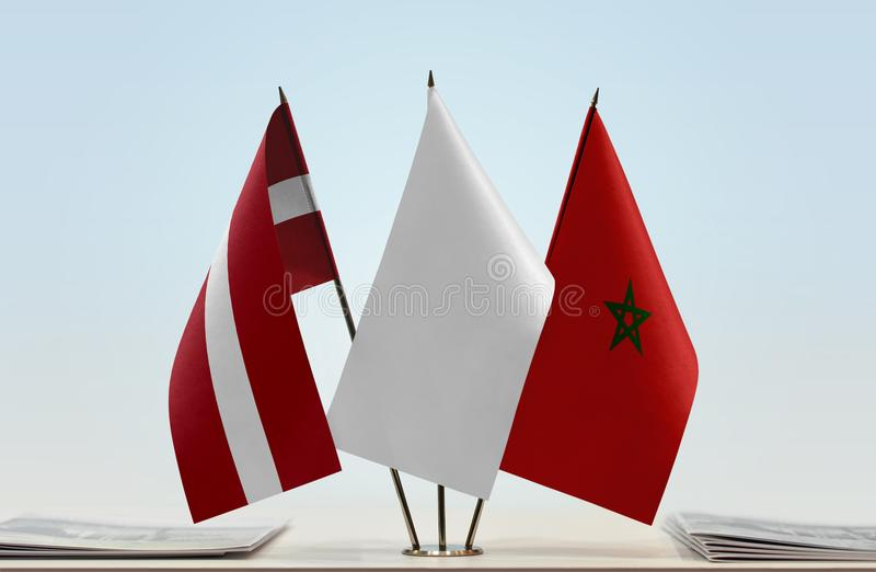 Flags of Latvia and Morocco. Desktop flags of Latvia and Morocco with white flag in the middle royalty free stock photos