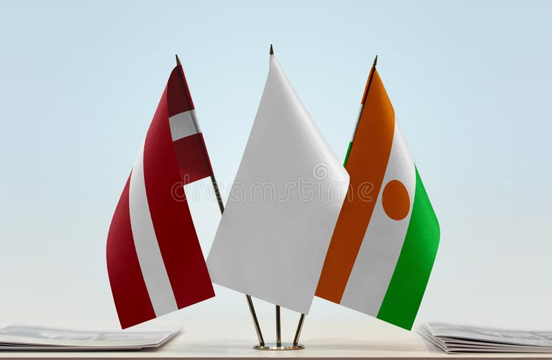 Flags of Latvia and Niger. Desktop flags of Latvia and Niger with white flag in the middle royalty free stock photography