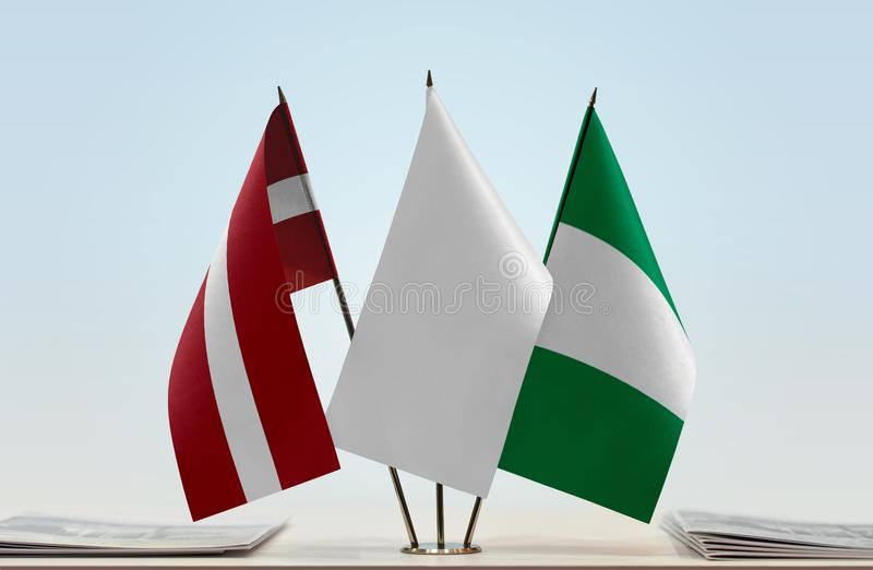 Flags of Latvia and Nigeria. Desktop flags of Latvia and Nigeria with white flag in the middle royalty free stock photo