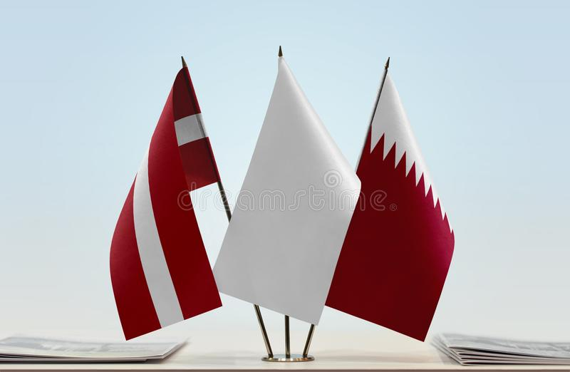 Flags of Latvia and Qatar. Desktop flags of Latvia and Qatar with white flag in the middle royalty free stock photos