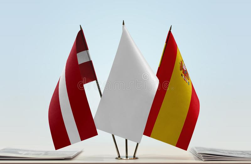 Flags of Latvia and Spain. Desktop flags of Latvia and Spain with a white flag in the middle royalty free stock image
