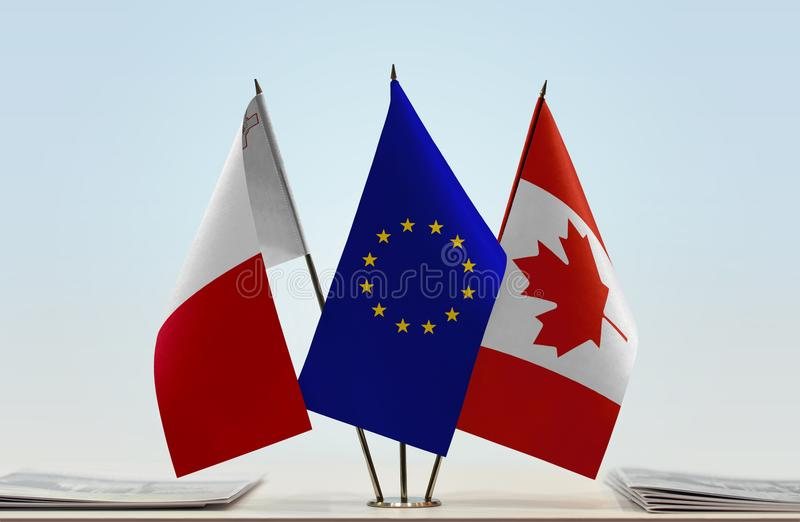 Flags of Malta EU and Canada. Desktop flags of Malta and Canada with European Union flag in the middle royalty free stock photos