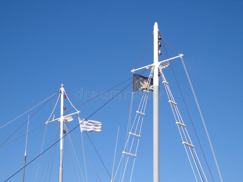 Flags on the masts. Masts of the yachts in the background of the blue sky stock photos