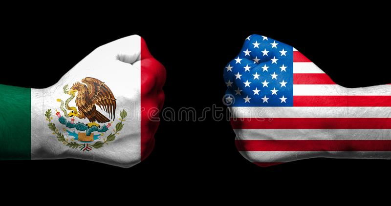 Flags of Mexico and United States painted on two clenched fists facing each other on black background/Mexico - USA relations conce. Pt stock photography