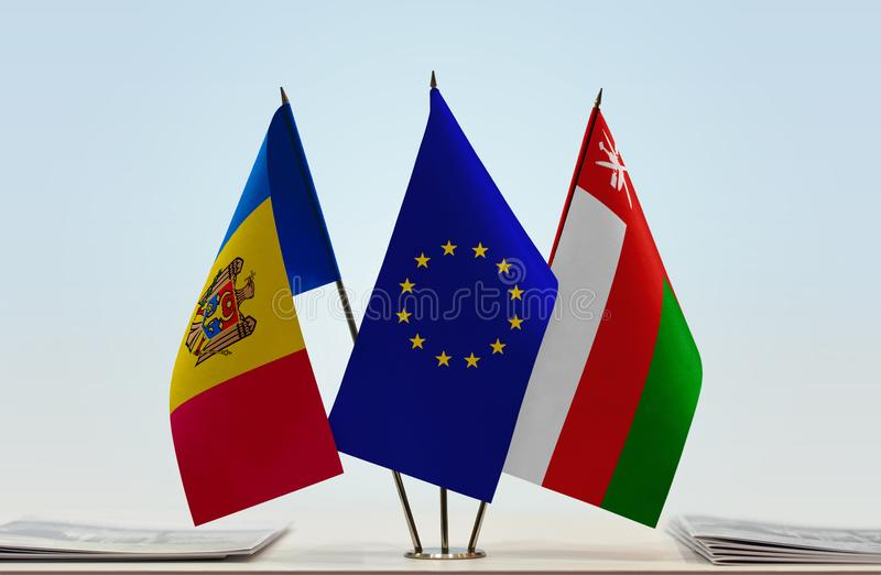 Flags of Moldova EU and Oman. Desktop flags of Moldova and Oman with European Union flag in the middle stock image