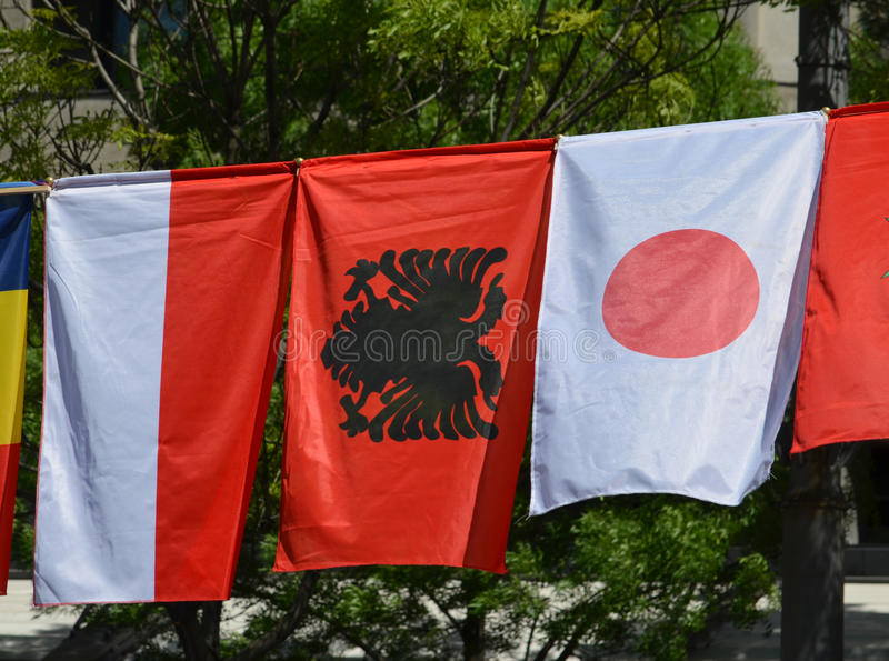 The flags of Monaco, Albania and Japan royalty free stock photo