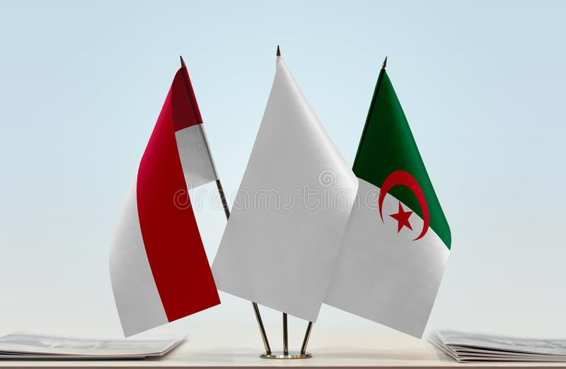 Flags of Monaco and Algeria. Desktop flags of Monaco and Algeria with white flag in the middle royalty free stock photography