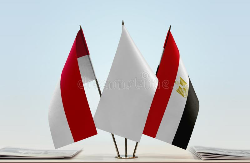 Flags of Monaco and Egypt. Desktop flags of Monaco and Egypt with white flag in the middle royalty free stock image