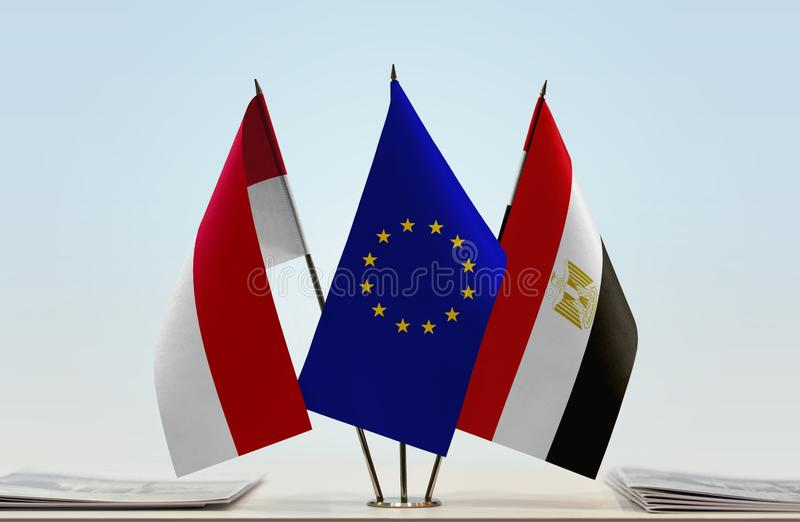 Flags of Monaco EU and Egypt. Desktop flags of Monaco and Egypt with European Union flag in the middle royalty free stock photography