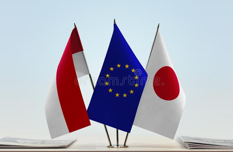 Flags of Monaco EU and Japan. Desktop flags of Monaco and Japan with European Union flag in the middle stock image