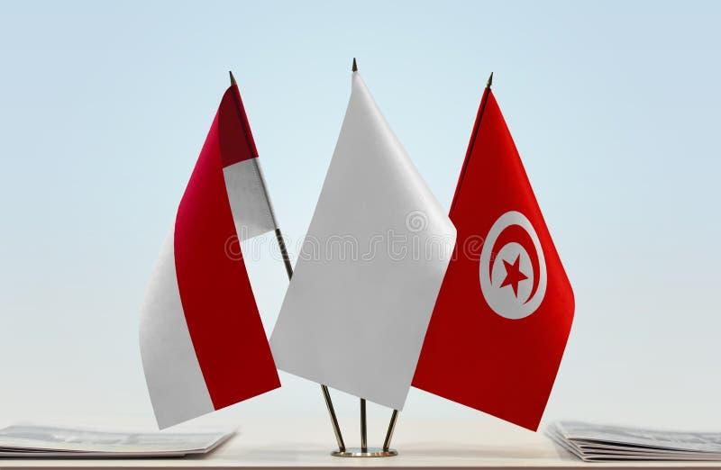 Flags of Monaco and Tunisia. Desktop flags of Monaco and Tunisia with white flag in the middle royalty free stock photo