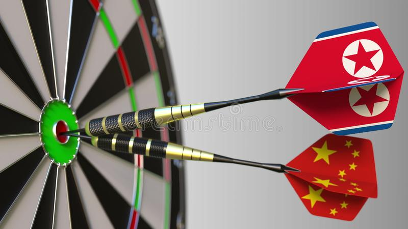 Flags of North Korea and China on darts hitting bullseye of the target. International cooperation or competition. Flags of North Korea and China on darts hitting stock image