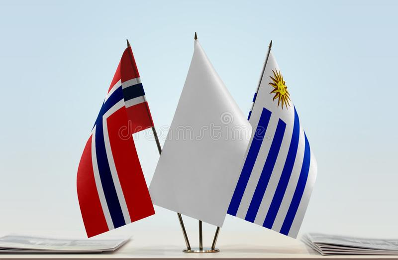 Flags of Norway and Uruguay. Desktop flags of Norway and Uruguay with white flag in the middle royalty free stock images
