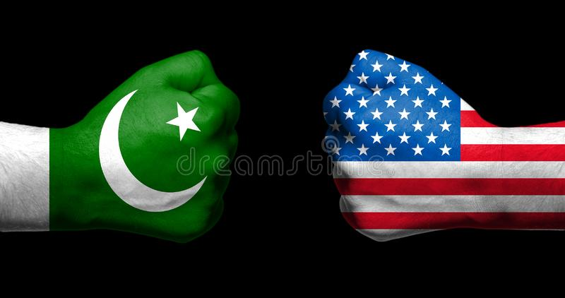 Flags of Pakistan and United States painted on two clenched fist. S facing each other on black background/Pakistan - USA relations concept royalty free stock photo