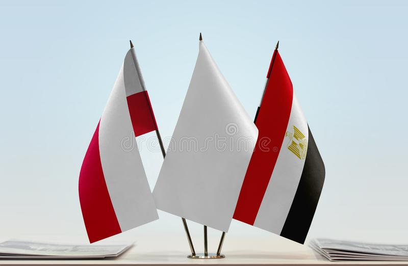 Flags of Poland and Egypt. Desktop flags of Poland and Egypt with white flag between stock photo