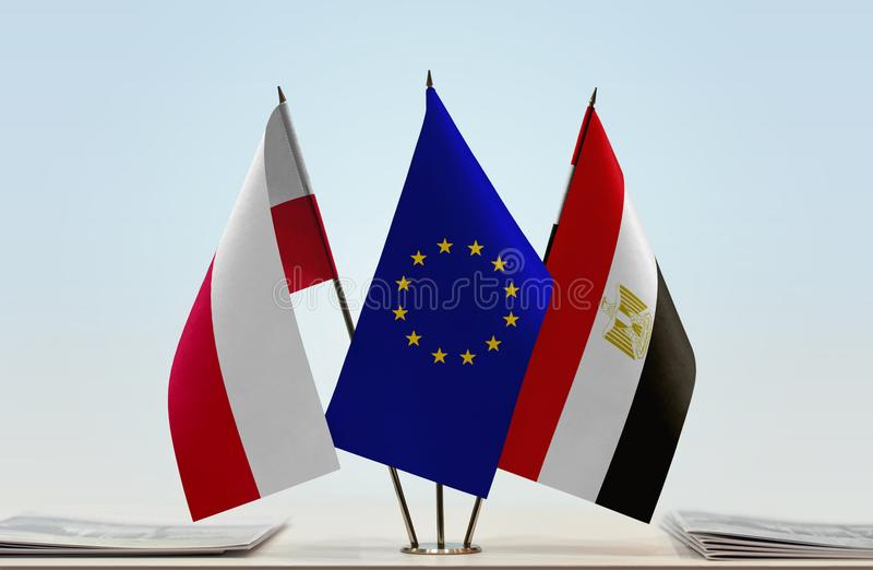Flags of Poland EU and Egypt. Desktop flags of Poland and Egypt with European Union flag in the middle royalty free illustration