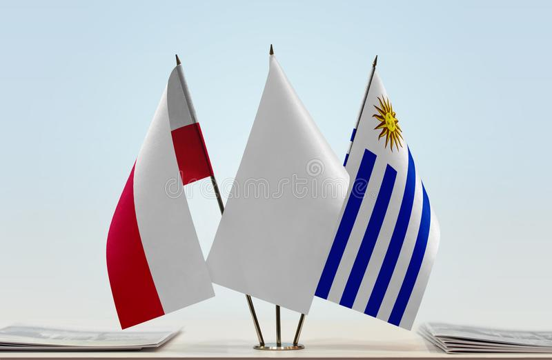 Flags of Poland and Uruguay. Desktop flags of Poland and Uruguay with white flag between royalty free stock photos