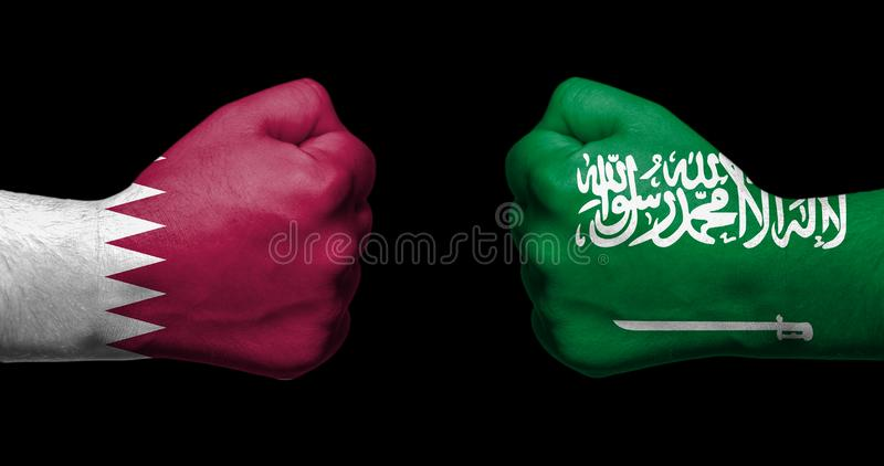Flags of Qatar and United Arab Emirates painted on two clenched. Fists facing each other on black background/Qatar - UAE diplomatic crisis concept royalty free stock images