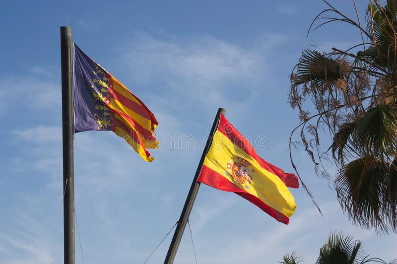 Flags in the Royal Navy of the city of Valencia near the beach. Two large flags of the Spanish state and the Valencian community on a sunny day next to the beach stock photos