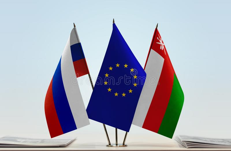 Flags of Russia EU and Oman. Desktop flags of Russia and Oman with European Union flag in the middle royalty free illustration