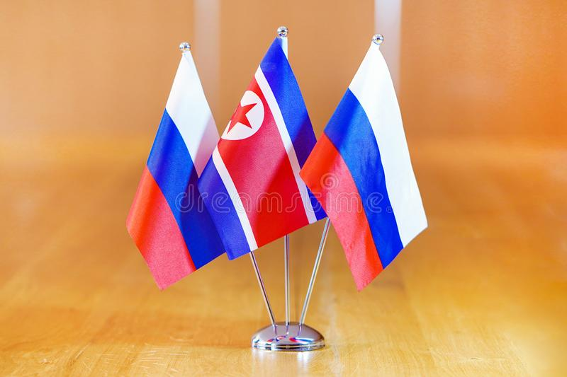 Flags of Russia and North Korea. Three flags on the table. Flags of Russia and North Korea. Flags of Russia and North Korea on the table during a meeting of stock image