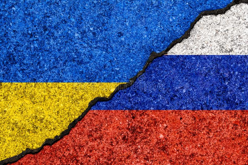 Flags of Russia and Ukraine painted on cracked wall background/Russia - Ukraine conflict concept stock images