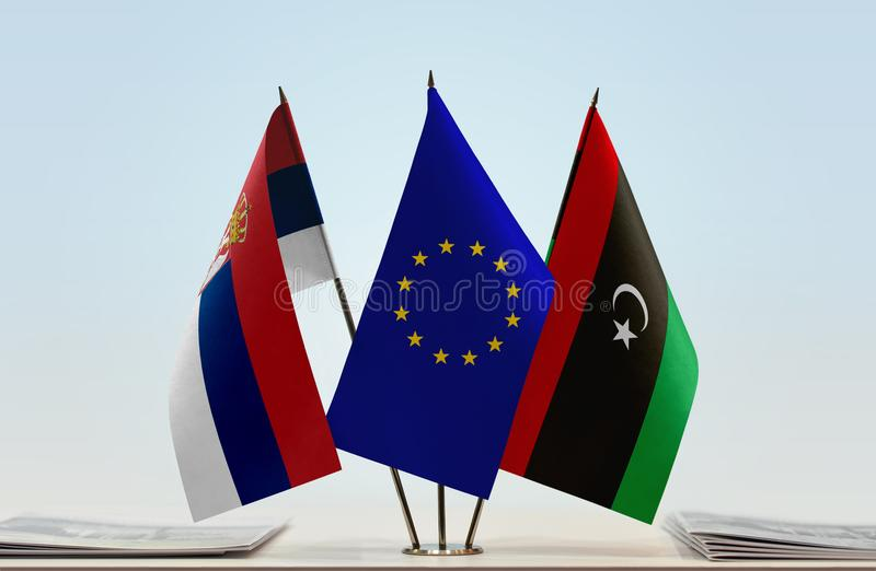 Flags of Serbia EU and Libya. Desktop flags of Serbia and Libya with European Union flag in the middle royalty free illustration