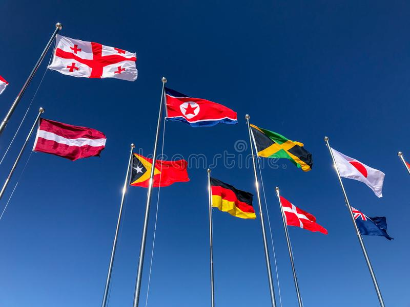 Flags of several countries waving in front of a blue sky royalty free stock photography