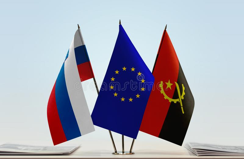 Flags of Slovenia EU and Angola. Desktop flags of Slovenia and Angola with European Union flag in the middle royalty free illustration