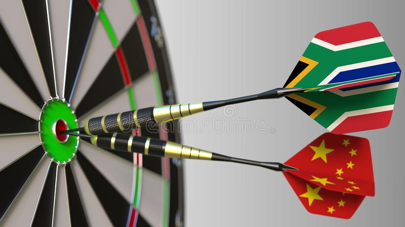 Flags of South Africa and China on darts hitting bullseye of the target. International cooperation or competition. Flags of South Africa and China on darts royalty free stock image