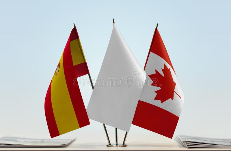 Flags of Spain and Canada. Desktop flags of Spain and Canada with white flag between stock photo