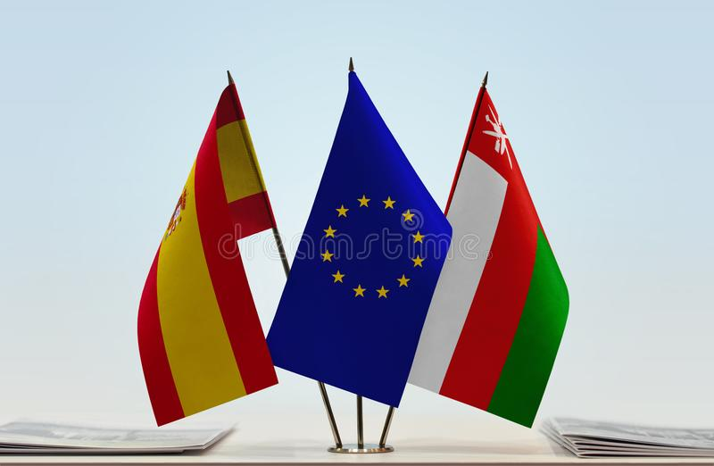 Flags of Spain EU and Oman. Desktop flags of Spain and Oman with European Union flag in the middle stock illustration