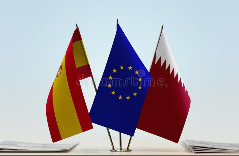 Flags of Spain EU and Qatar. Desktop flags of Spain and Qatar with European Union flag in the middle royalty free illustration