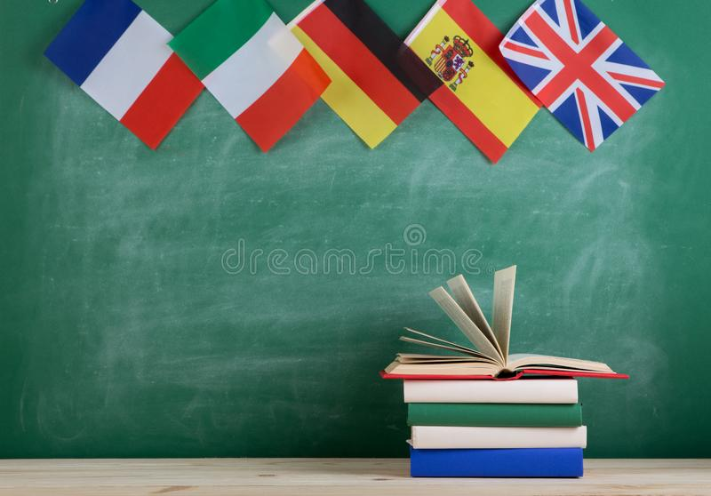 flags of Spain, France, Great Britain and other countries and books on the background of the blackboard royalty free stock photos
