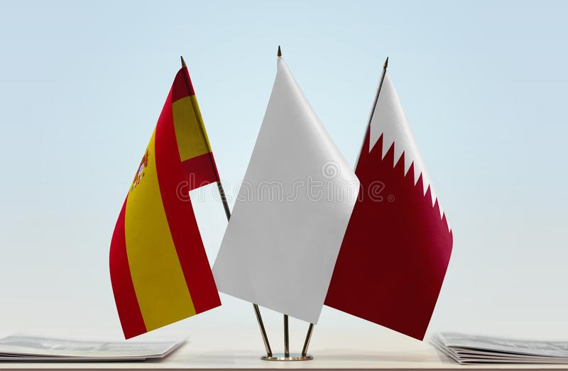 Flags of Spain and Qatar. Desktop flags of Spain and Qatar with white flag between royalty free stock photo