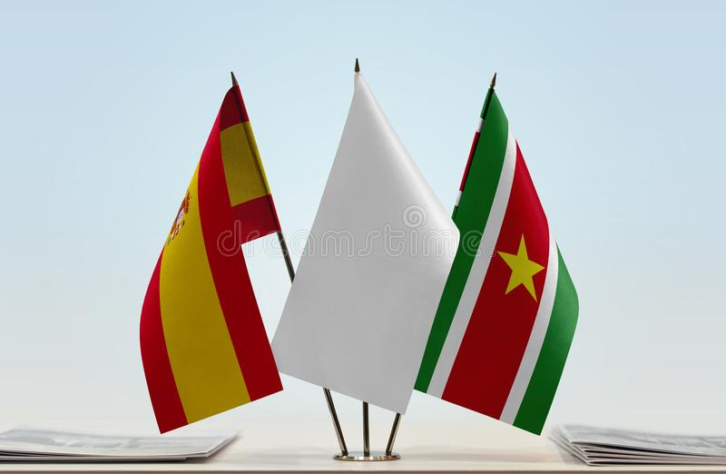 Flags of Spain and Suriname. Desktop flags of Spain and Suriname with white flag between stock photo