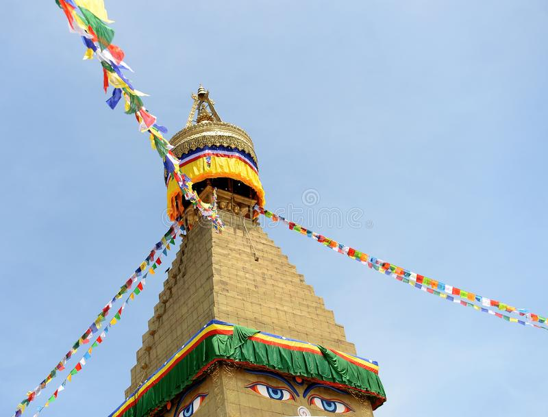 Flags on Stupa, Kathmandu, Nepal. Colorful flags on exterior of Buddhist stupa painted with eyes against blue skies on sunny day in Kathmandu, Nepal royalty free stock photos