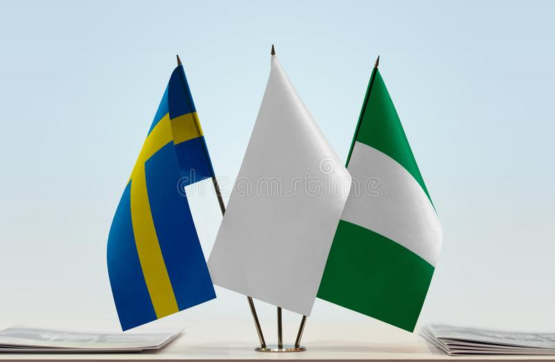 Flags of Sweden and Nigeria. Desktop flags of Sweden and Nigeria with white flag between royalty free stock images