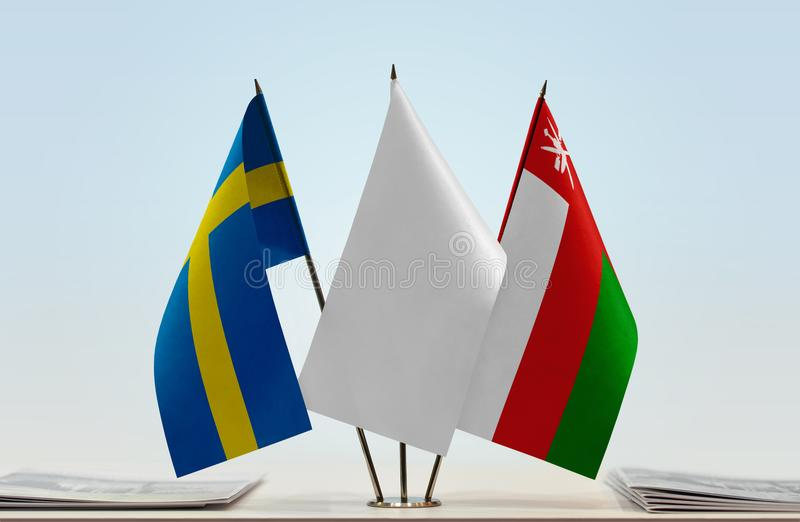 Flags of Sweden and Oman. Desktop flags of Sweden and Oman with white flag between stock photos