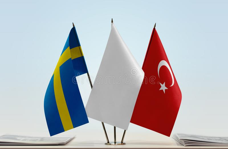 Flags of Sweden and Turkey. Desktop flags of Sweden and Turkey with a white flag in the middle stock image