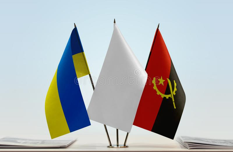 Flags of Ukraine and Angola. Desktop flags of Ukraine and Angola with white flag between stock photos