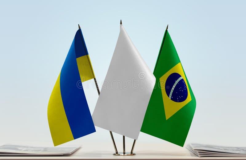 Flags of Ukraine and Brazil. Desktop flags of Ukraine and Brazil with white flag between stock images
