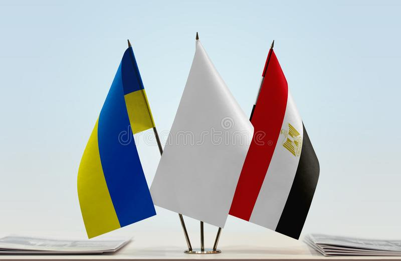 Flags of Ukraine and Egypt. Desktop flags of Ukraine and Egypt with white flag between royalty free stock photography