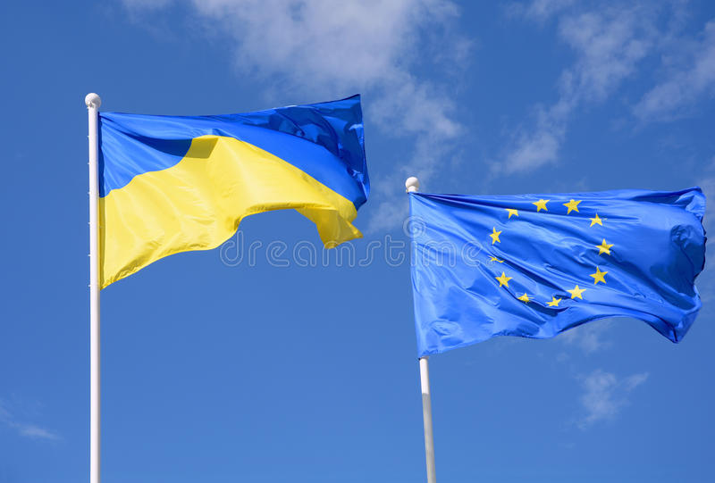 Flags of Ukraine and European Union EU against the blue sky. royalty free stock image